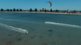 Professional surfers kiteboarding in clear blue ocean on sunny day tropical seascape in wonderful aerial drone 4k view. Professional surfers kiteboarding in stock video footage