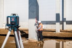 Professional surveyor using gps system and theodolite for correct level on construction site. Surveyor using gps system and theodolite for correct level on Stock Photo