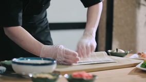 Professional sushi roll twisting. Sushi master preparing rolls using a bamboo mat. Cooking sushi rolls. Professional sushi roll twisting stock footage