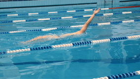 Professional swimmer in cap breathing performing the butterfly stroke stock video