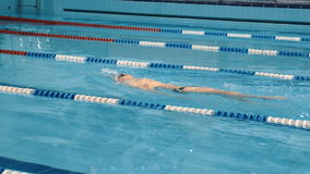 Professional swimmer in cap breathing performing the butterfly stroke stock video footage