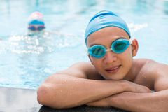 Professional swimmer. Close-up portrait of a young swimmer in protective goggles leaning on the pool and posing at camera on the foreground Royalty Free Stock Photos