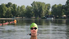 Professional swimmer in the lake on a sunny day. Only the athlete's head is visible above the water. Close up. Professional swimmer in the lake on a sunny stock footage
