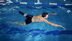 Professional swimmer with leg prosthesis training in a pool. 4K stock video footage