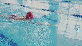 Professional swimmer trains in the pool. She swims like a crawl and skillfully makes a stroke with her hands. Body. Possession while swimming. Bubbles and water stock footage