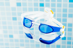 Professional swimming glasses, blue tile background Royalty Free Stock Photography