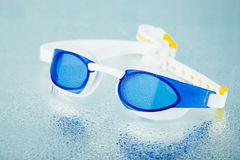 Professional swimming glasses, blue tile background Royalty Free Stock Image