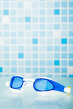 Professional swimming glasses, blue tile background Stock Photo