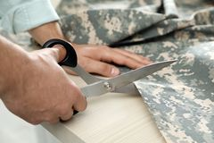 Professional tailor cutting camouflage fabric with scissors in workshop. Closeup stock photography