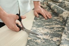 Professional tailor cutting camouflage fabric with scissors in workshop. Closeup royalty free stock image