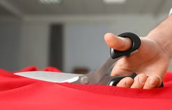 Professional tailor cutting red fabric with scissors in workshop. Closeup royalty free stock photo