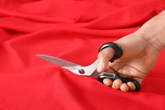 Professional tailor cutting red fabric with scissors in workshop. Closeup stock images