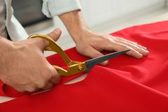 Professional tailor cutting red fabric with scissors in workshop. Closeup royalty free stock image
