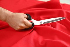 Professional tailor cutting red fabric with scissors in workshop. Closeup royalty free stock photos