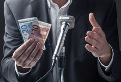 Professional talking to a micro with money in hands Royalty Free Stock Image