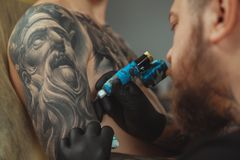 Professional tattoo artist doing a new tattoo for his client stock photos