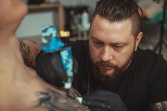 Bearded tattooist making tattoos on body of his client. Professional tattoo artist looking focused, working at his studio, making a tattoo on the chest of his royalty free stock photography