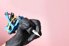 Professional tattoo artist with machine on color background, closeup. Space for text stock photo