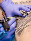 Professional tattoo artist makes a tattoo Royalty Free Stock Photo