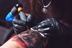 Professional tattoo artist makes a tattoo on a man`s hand stock image