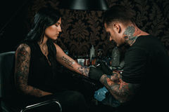 Professional tattoo artist makes a tattoo on a young girl`s hand Royalty Free Stock Photo