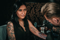 Professional tattoo artist makes a tattoo on a young girl`s hand Royalty Free Stock Image