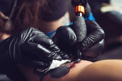 Professional tattoo artist makes a tattoo on a man`s hand royalty free stock photo
