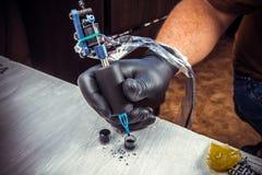 Professional tattoo artist making a tattoo in tattoo parlour Stock Photo