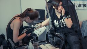 Professional tattoo artist stuffs a tattoo on a persons`s body royalty free stock photography