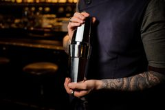 Professional bartender holding the steel cocktail shaker. Professional tattooed bartender holding the steel cocktail shaker on the blurred background of a bar stock image