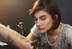 A professional tattooer artist doing picture on man hand. By machine. Tattoo art on body. Equipment for making black ink from a jartattoo art royalty free stock photography