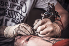 Professional tattooer burning the tatoo Stock Photography
