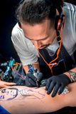 Professional tattooer shows tattoo coloring Stock Images