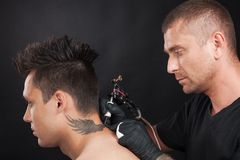 Professional tattooist drawing eagle wings. Royalty Free Stock Images