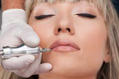 Professional tattooist making permanent make up. Stock Photos