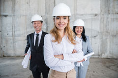 Professional team of architects in helmets standing together Stock Images