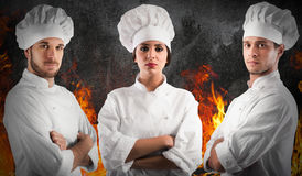 Professional team chef. Professional chef women and men with confident expressions with fire flames on background royalty free stock photos