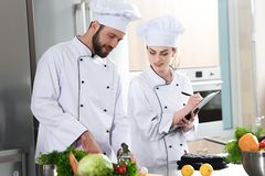 Professional team of cooks checking recipe during. Cooking dish royalty free stock images
