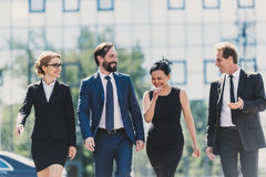 Middle aged multiethnic businesspeople walking together and talking in city. Professional team of middle aged multiethnic businesspeople walking together and stock image