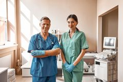Professional team. Two positive vets in work uniform are smiling and looking at camera while standing at the veterinary. Clinic. Pet care concept. Medicine stock image