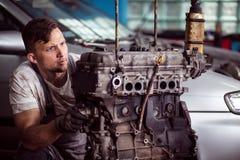 Professional technician diagnosing problem. Photo of professional auto technican diagnosing engine problem Royalty Free Stock Images