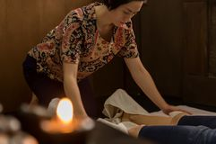 Professional therapist giving traditional Thai massage or Thai yoga massage treatment.  Stock Images