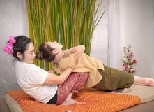 Professional therapist giving traditional thai massage to a woma Stock Image