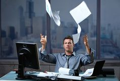 Professional throwing documents into air. Exhausted professinal throwing documents into air sitting at office desk in overtime Royalty Free Stock Photography