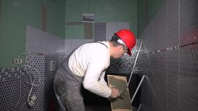 Professional tiler adding cement glue on tile before installing ceramic tile. In bathroom. Static shot stock video footage