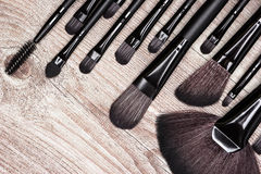 Professional tools of makeup artist on shabby wooden surface Royalty Free Stock Image