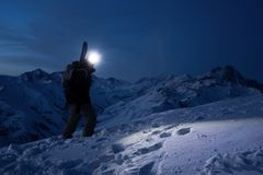 Professional tourist commit climb on great snowy mountain at night. Wearing backpack, headlamp and ski wear. Backcountry. Brave extreme traveler with a Stock Photos