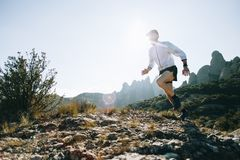 Athletic strong man runs trail ultra marathon. Professional trail runner, ultra distance athlete runs through rocky terrain high on mountain path or hiking trail Stock Images