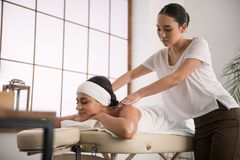 Pleasant young woman doing a professional massage. Professional treatment. Pleasant young women looking at her client while doing a professional massage stock images