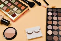 Professional trendy makeup products with cosmetic beauty products, foundation, lipstick,  eye shadows, eye lashes, brushes and. Tools. Top view royalty free stock photography